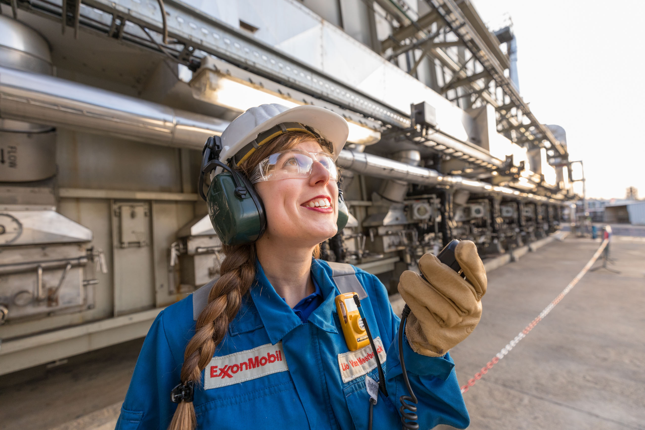 Woman at industrial facility with bright smile on radio by tech photographer Rich Crowder