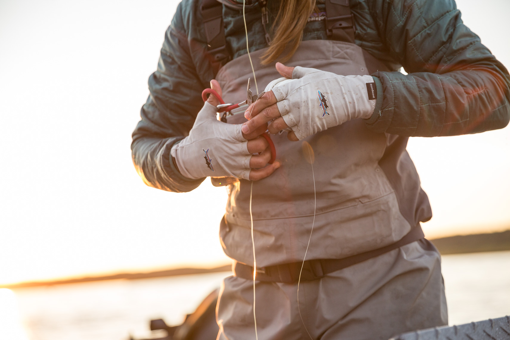Kate Taylor, prepping her rod in Alaska fishing for salmon by outdoor photographer Rich Crowder