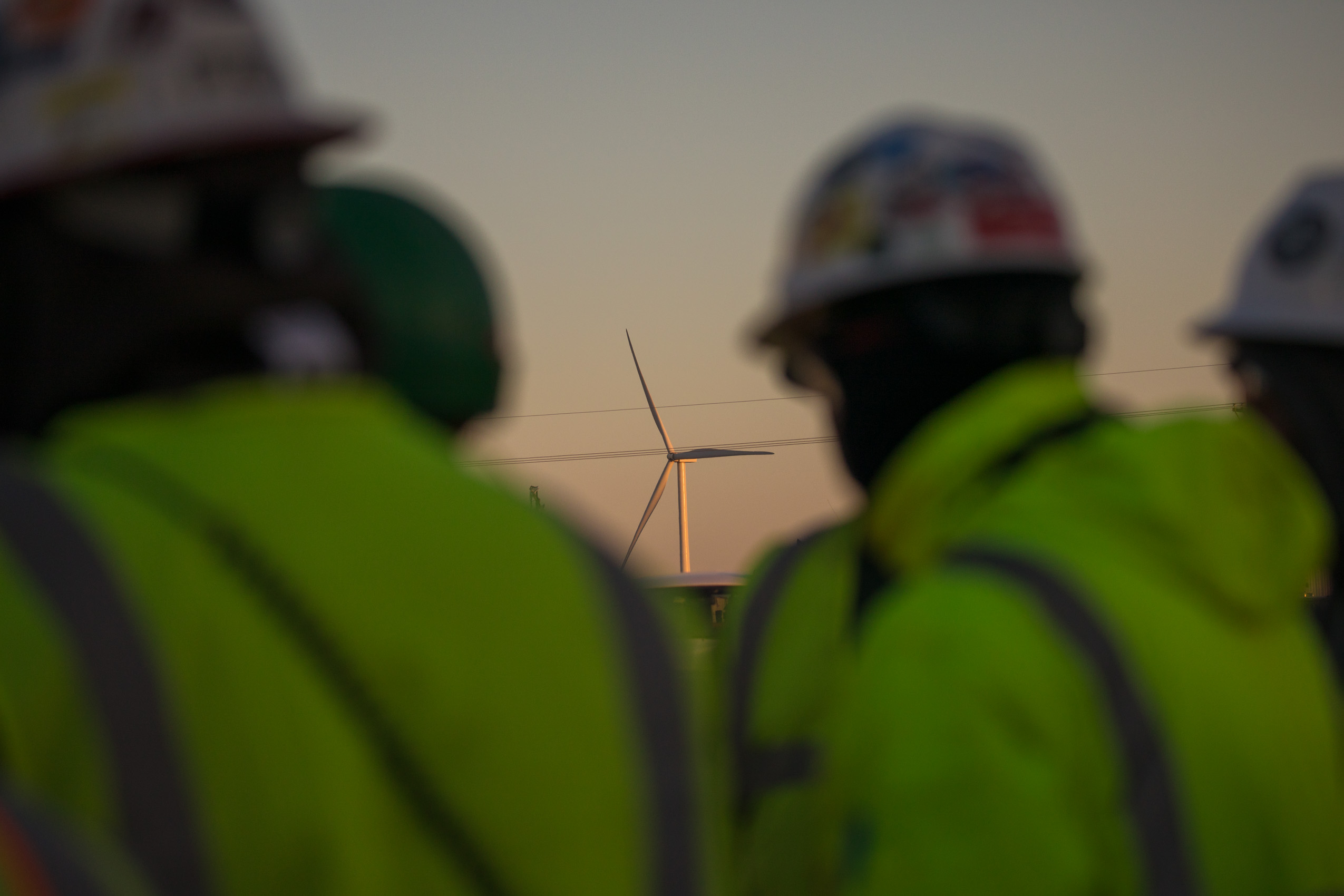 workers at sunrise with wind turbine